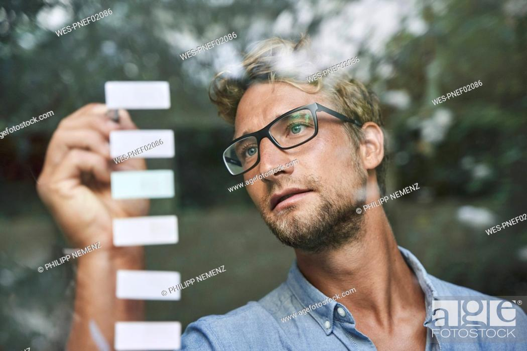 Stock Photo: Casual young businessman with adhesive notes behind windowpane in office.