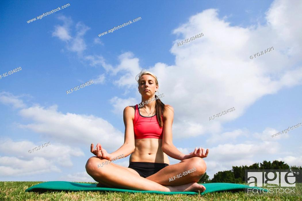 Stock Photo: Young Woman sitting on mat in sukhasana position.