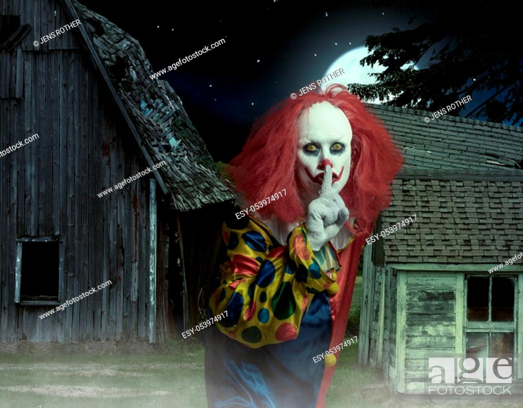 Stock Photo: eerie clown with finger on mouth in front of a scary scene.