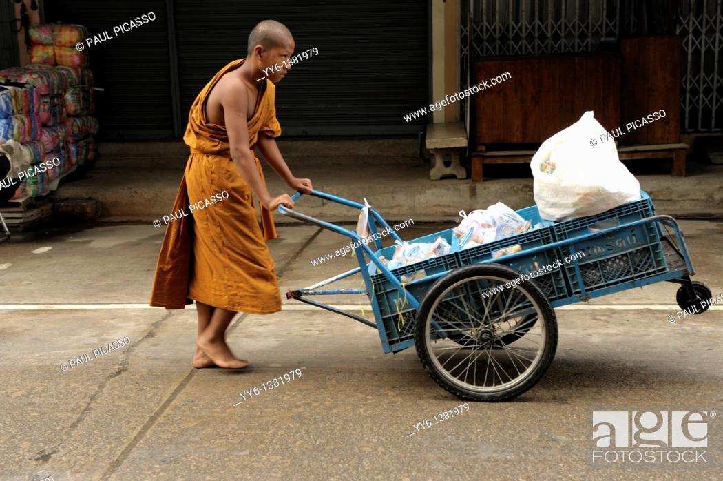Stock Photo: young novice monk pushing cart with food collecting on morning alms round , mae sot, northern thailand.