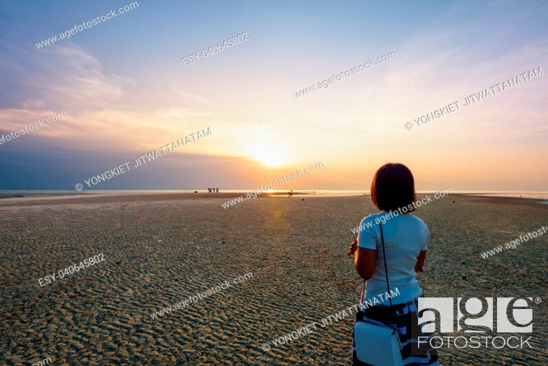 Stock Photo: Women tourist standing on the beach watching the beautiful natural landscape, colorful of the sky and the sea during a sunset at Nathon Sunset Viewpoint in Ko.
