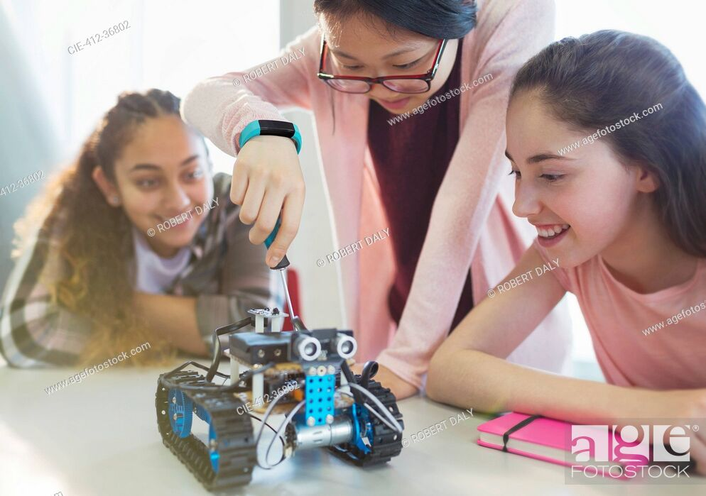 Stock Photo: Girl students assembling robotics in classroom.