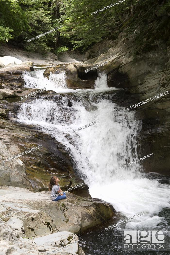 Stock Photo: Girl sitting on a rock next to the Waterfall of the bucket in the Selva de Irati in Navarra, Spain.