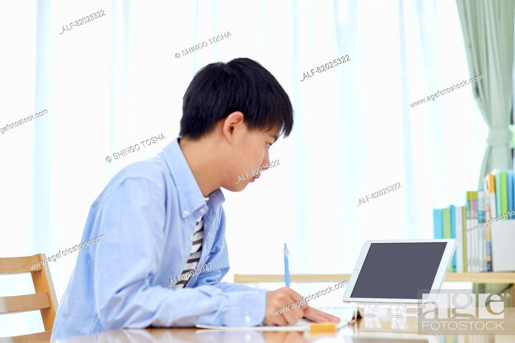Stock Photo: Japanese kid studying at home.