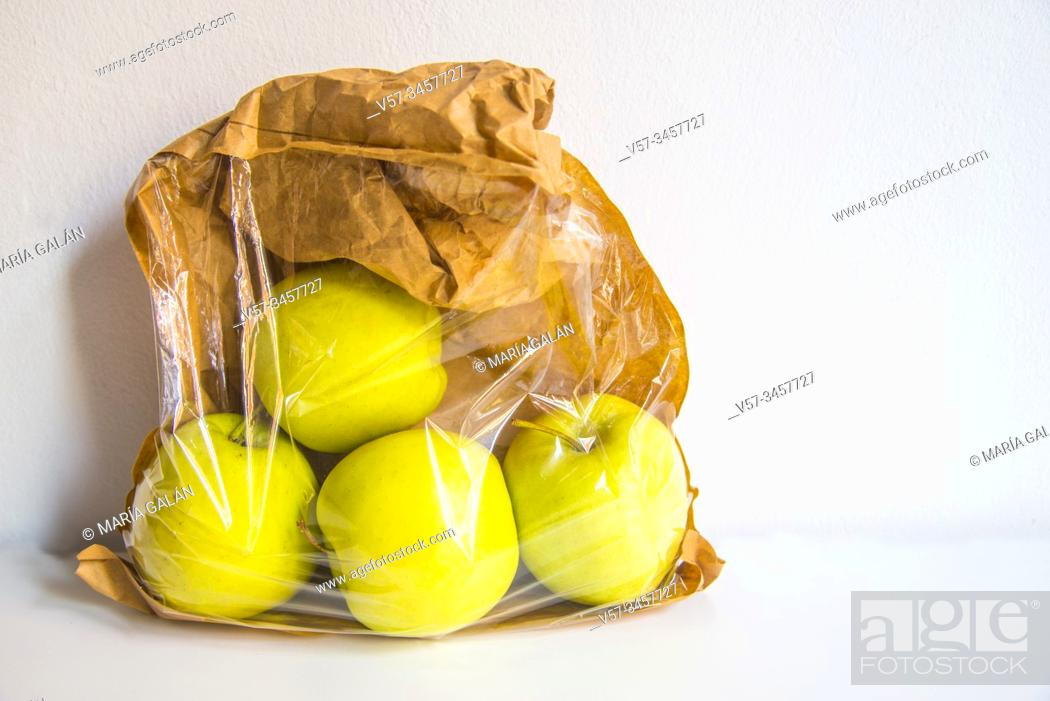Imagen: Four apples in a paper bag.
