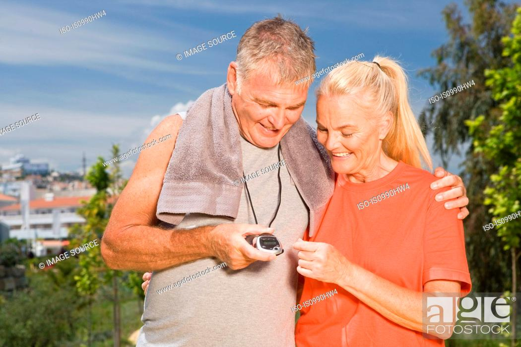 Stock Photo: Mature couple looking at stopwatch after workout.
