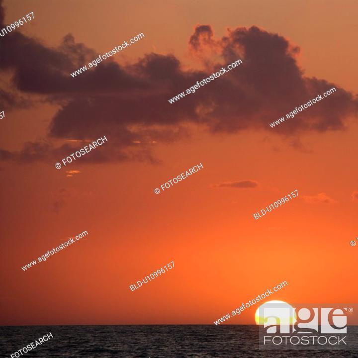 Stock Photo: Sun setting over horizon of ocean.