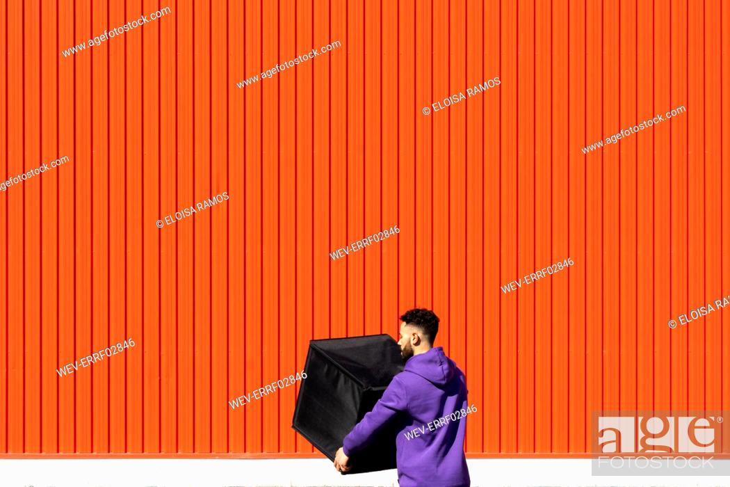 Stock Photo: Young man carrying a box in front of a red wall.
