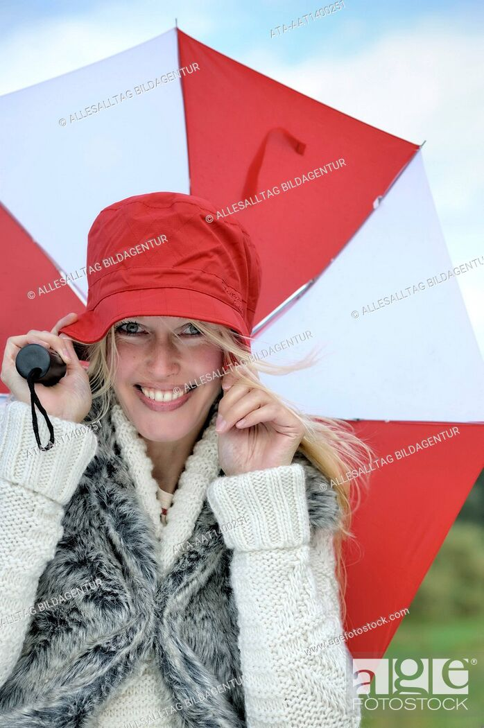 Stock Photo: Woman walking with an umbrella against strong wind.