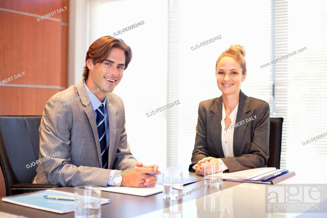 Stock Photo: Portrait of smiling businessman and businesswoman in conference room.