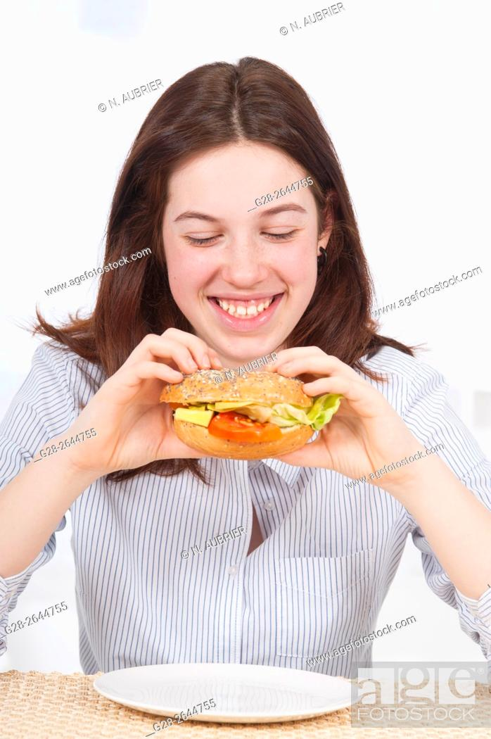 Stock Photo: Teenage girl smiling with bagel in hand.