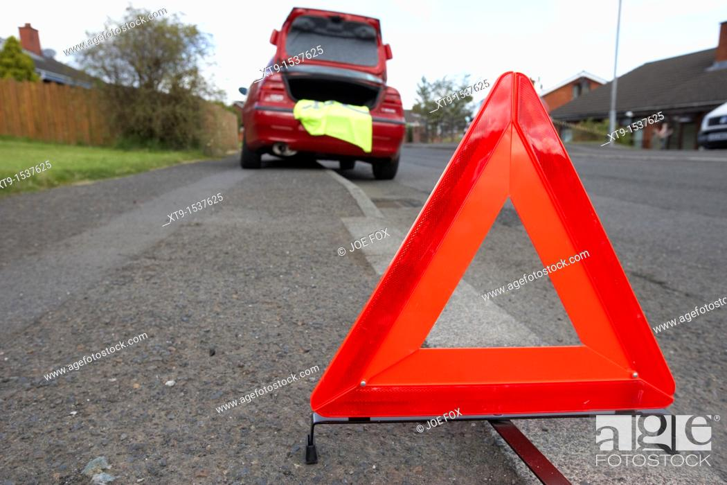 Stock Photo: hazard warning triangle laid out on the side of the road in a residential area behind a broken down car.