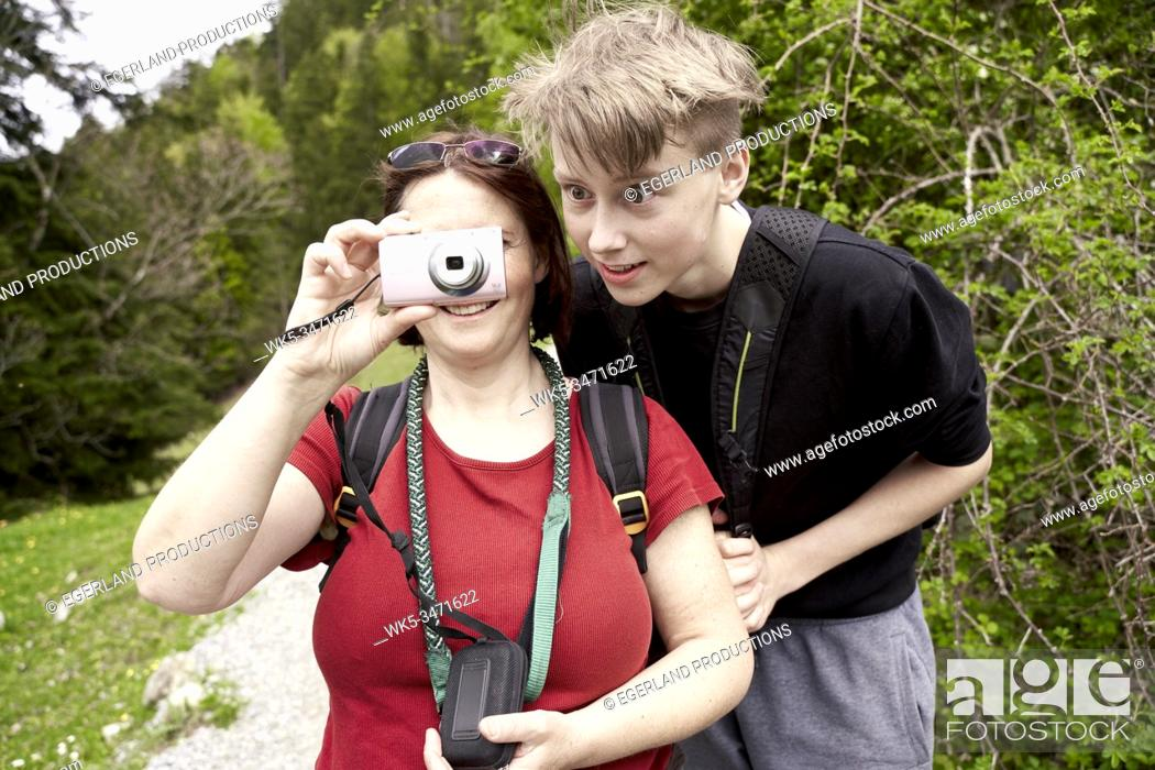 Imagen: Mature woman and teenager son in the countryside, with digital camera. Bad Tölz, Upper bavaria, Germany.