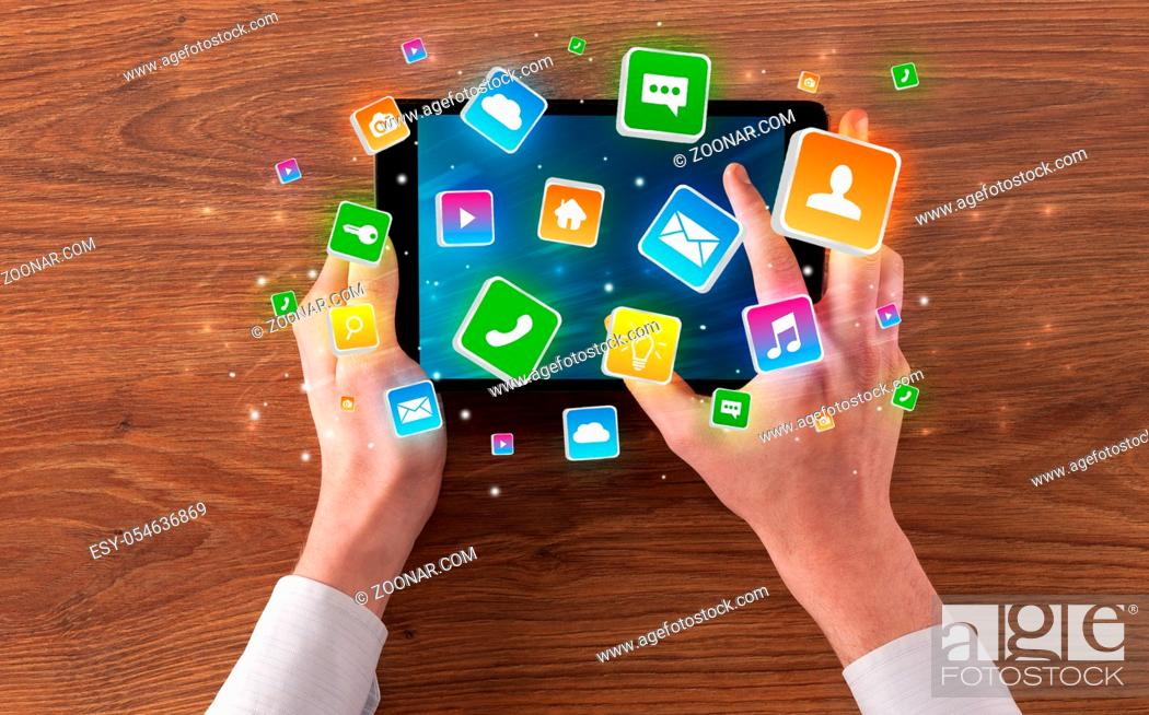 Photo de stock: Hand using tablet with colourfull bounce application symbols and icons concept.