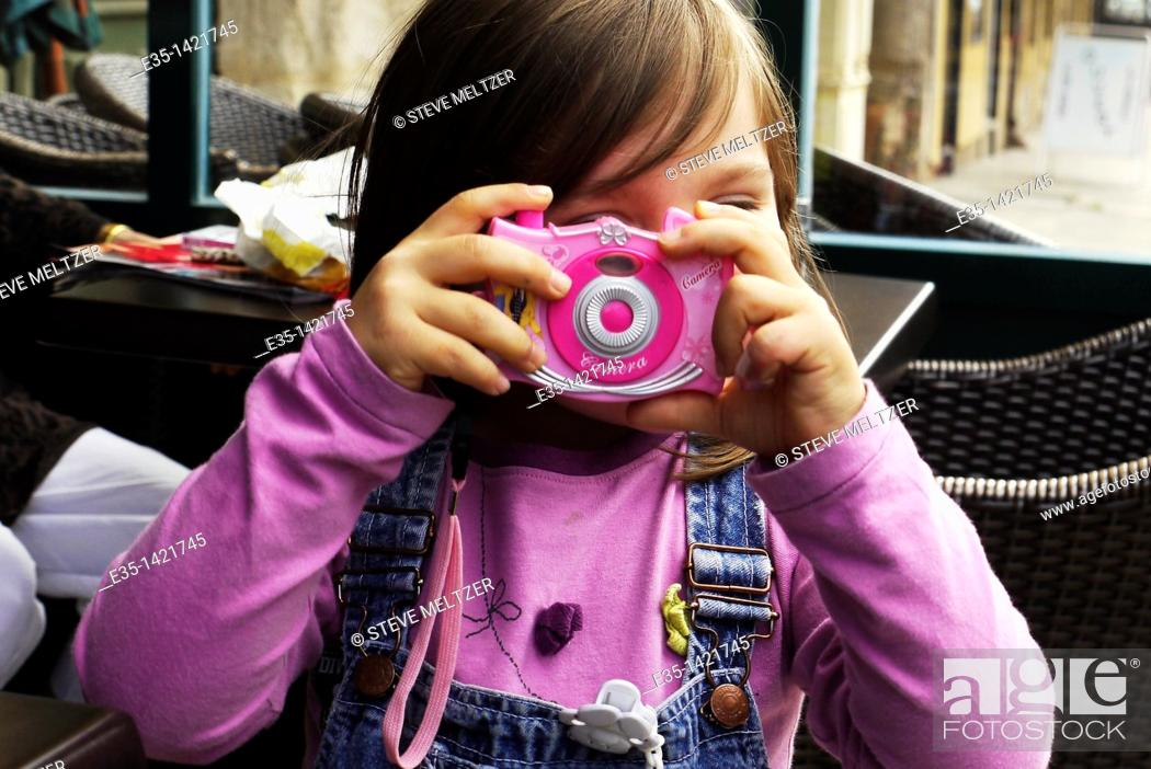 Stock Photo: A little girl plays at being a photographer.