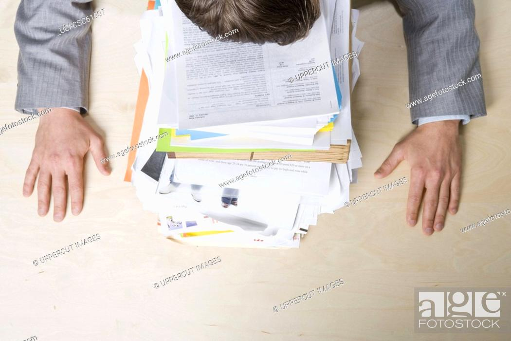 Stock Photo: Businessman resting head on stack of paperwork.