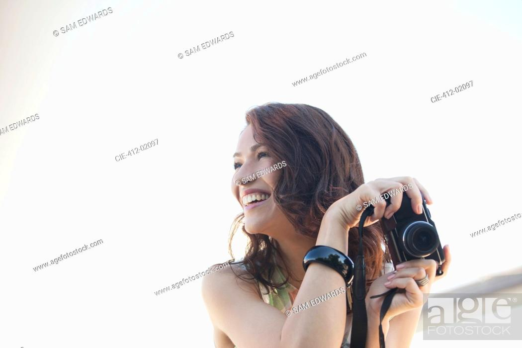 Stock Photo: Smiling woman taking pictures outdoors.