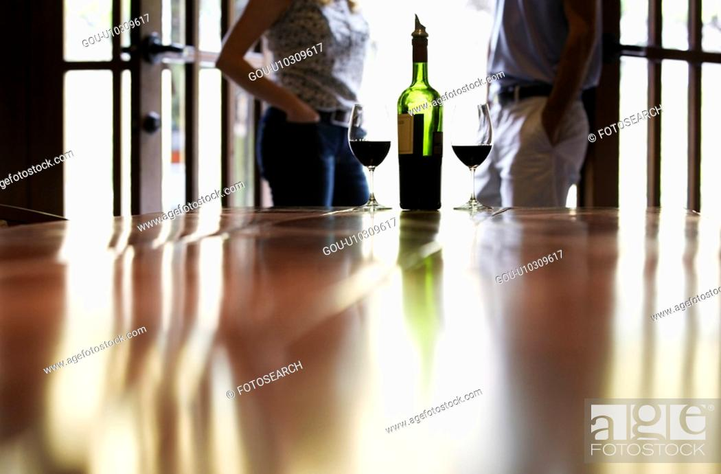 Stock Photo: Couple standing near bottle of red wine (focus on foreground).