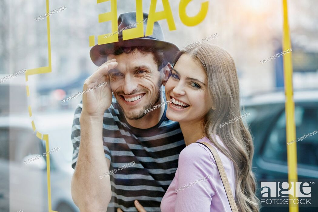 Stock Photo: Young couple looking through window of a coffee shop.