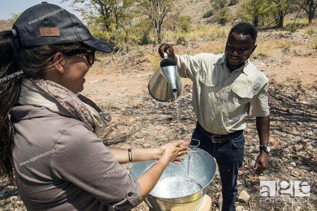 Stock Photo: Woman washing her hands in tin basin - Huab Under Canvas, Damaraland, Namibia, Africa.