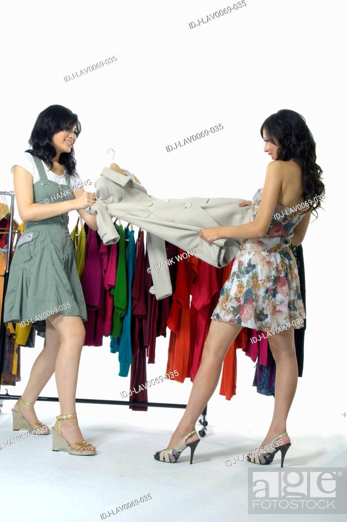 Stock Photo: Women pulling a coat in a clothing store.