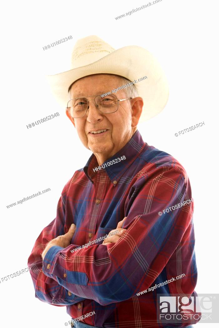 Stock Photo: Portrait of smiling Caucasion elderly man wearing plaid shirt and cowboy hat with arms crossed.