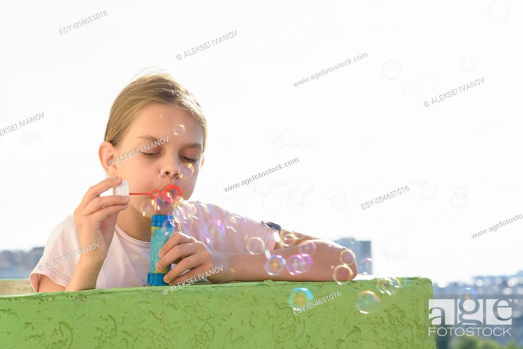 Stock Photo: Girl blows bubbles on the balcony of a high-rise building.