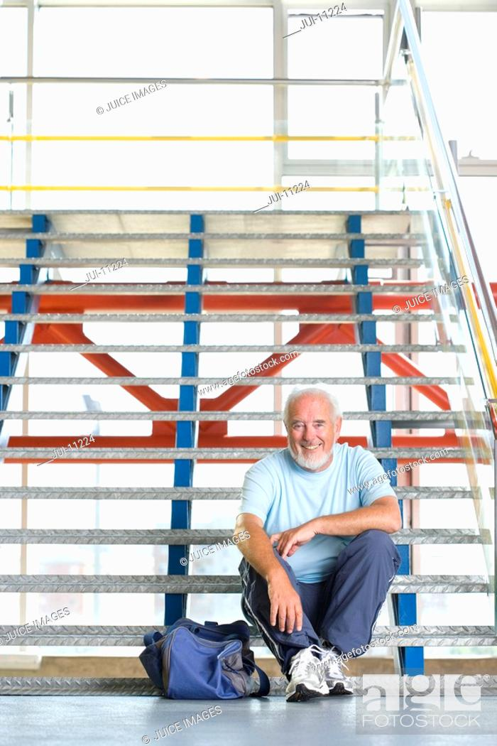 Stock Photo: Senior man with bag on stairs, portrait, low angle view.