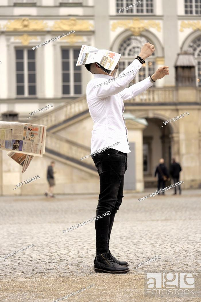 Stock Photo: Man overwhelmed by newspapers at Nymphenburg, Munich, Germany.