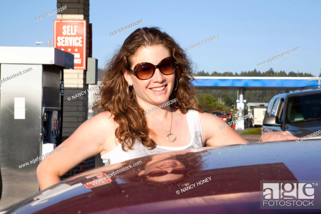 Stock Photo: Smiling woman pumping gas at station.