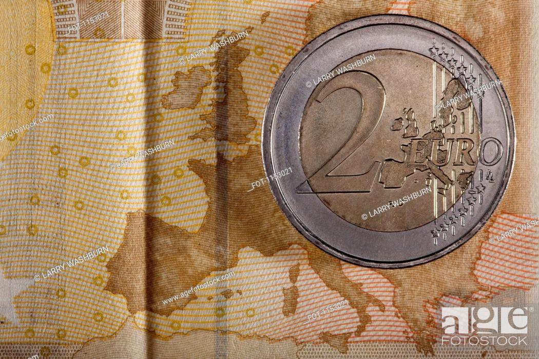 Stock Photo: Detail of a fifty Euro banknote with a two Euro coin on top of it.