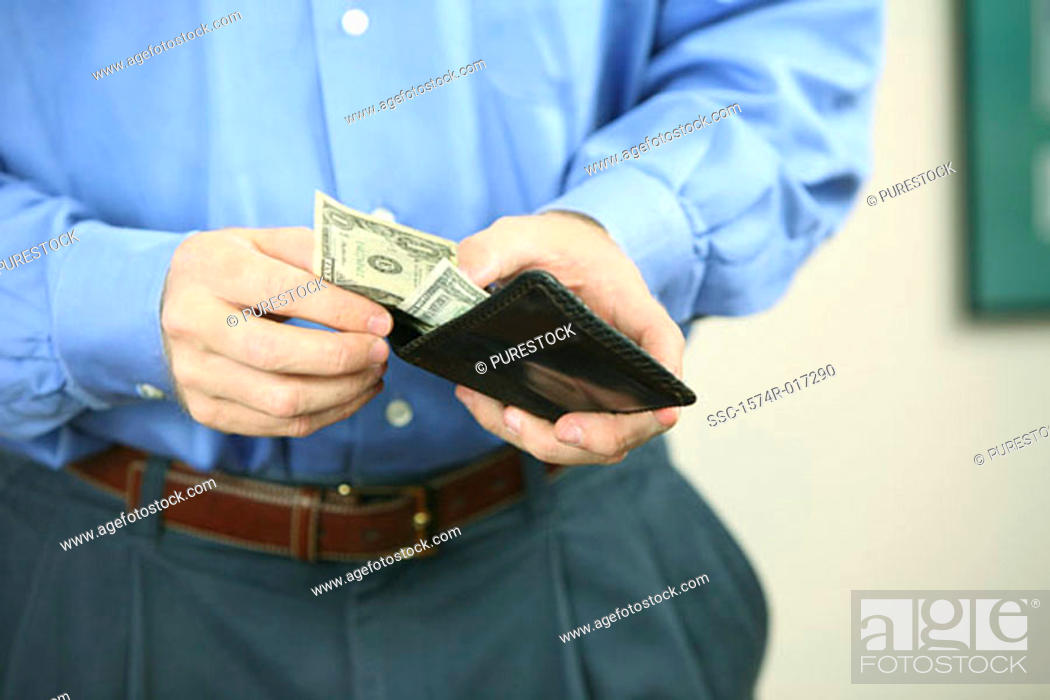Stock Photo: Mid section view of a mid adult man holding a wallet.