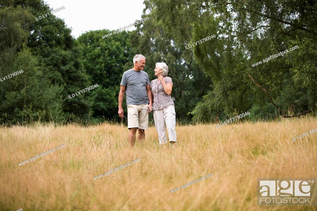 Stock Photo: A senior couple standing in a field, holding hands.