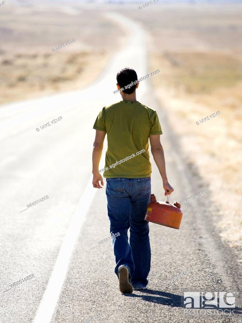 Stock Photo: man walking with a gas can.