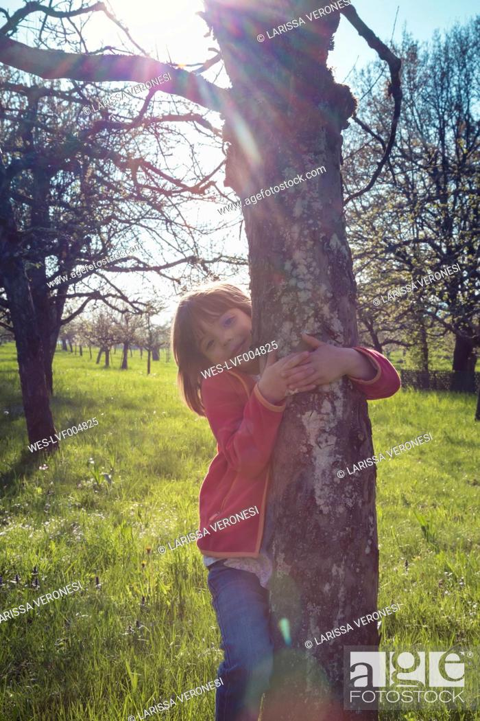 Stock Photo: Portrait of smiling little girl embracing tree.