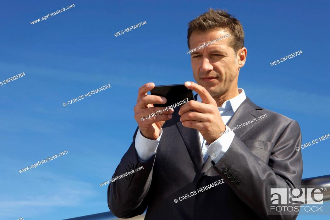 Stock Photo: Germany, Bavaria, Munich, Businessman using cell phone.