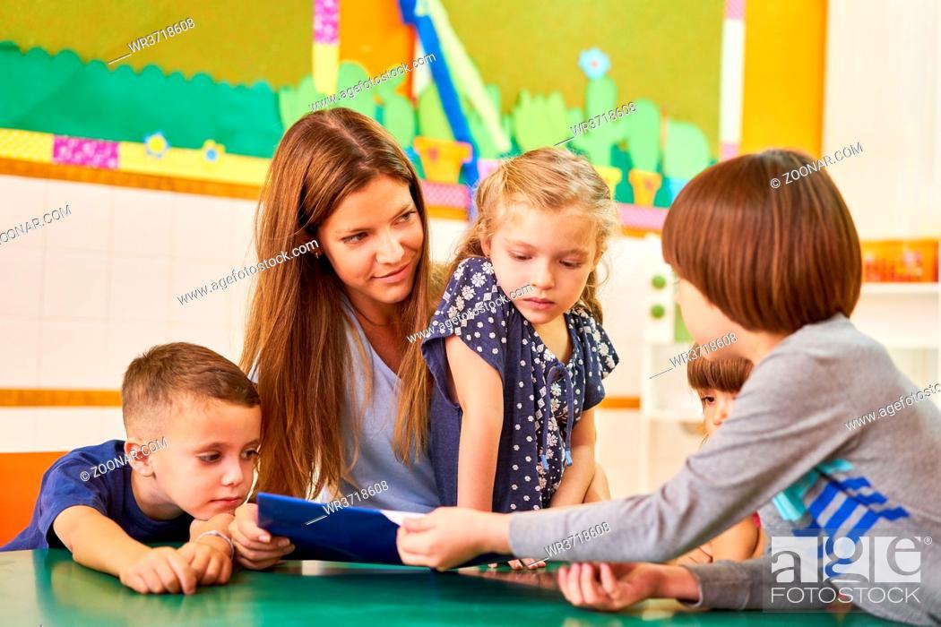 Stock Photo: Kindergärtnerin oder Tagesmutter beim Buch vorlesen für Kinder im Hort oder im Kindergarten.