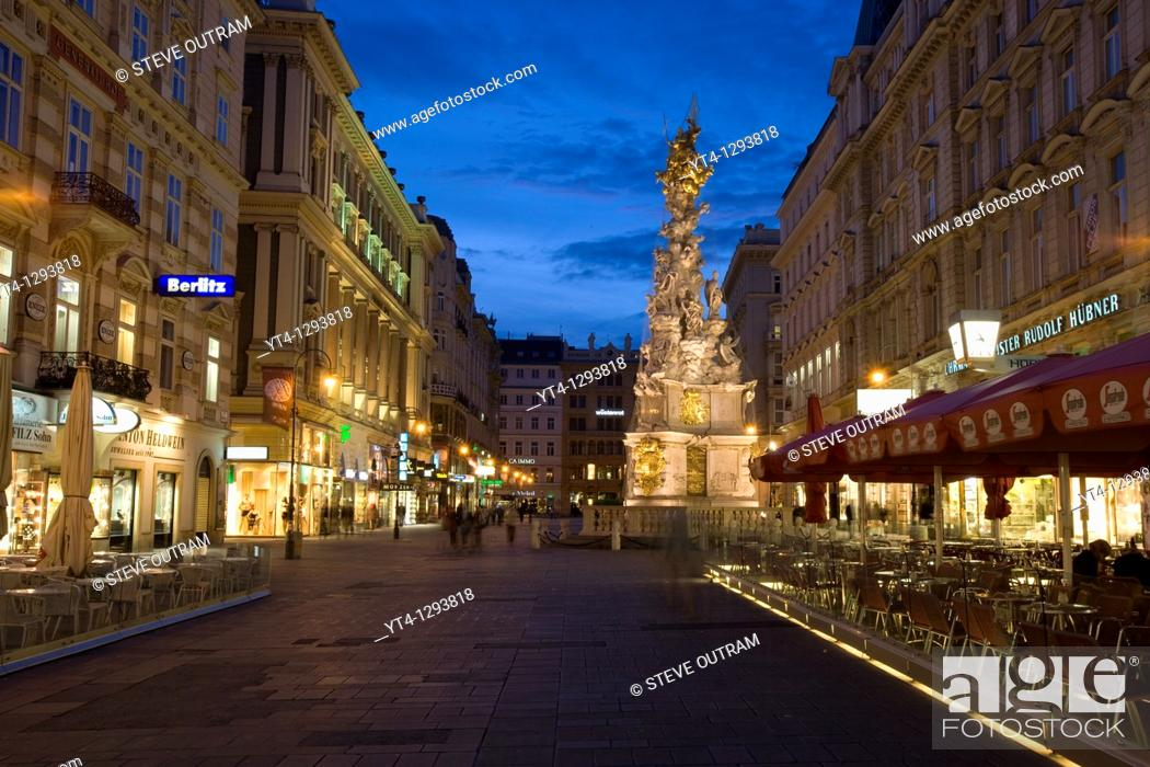 Stock Photo: Nighttime view of shops and cafes on Graben Street and view of the Plague or Pestsaule Column, Vienna, Austria.