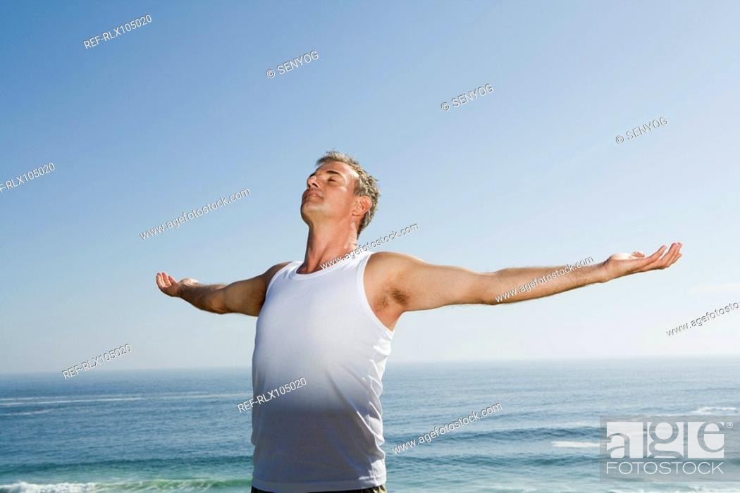 Stock Photo: Mature man with arms outstretched, with ocean in background.