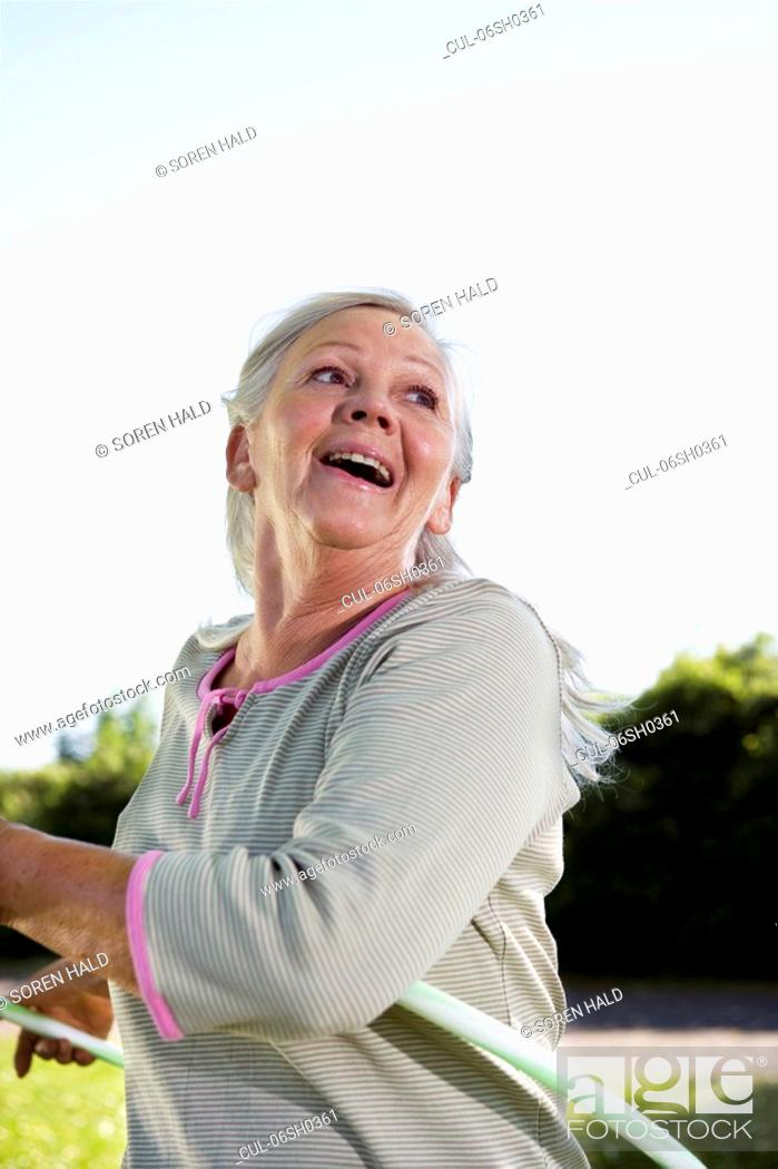Stock Photo: Mature woman with hula-hoop.