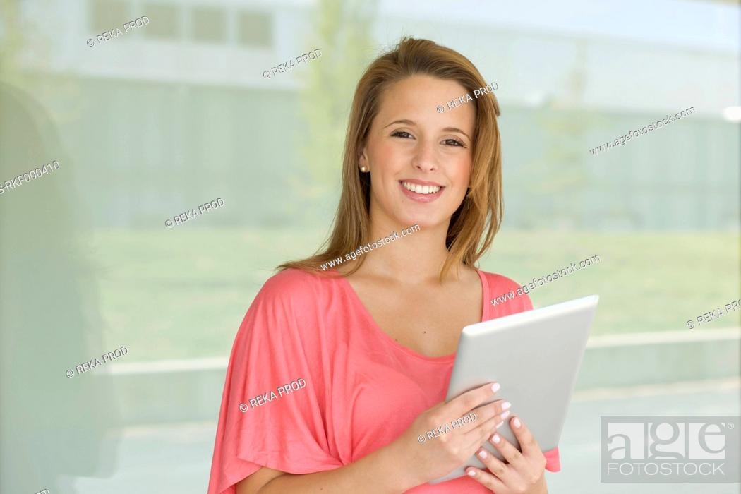 Stock Photo: Europe, Germany, North Rhine Westphalia, Duesseldorf, Young woman with digital tablet, smiling, portrait.