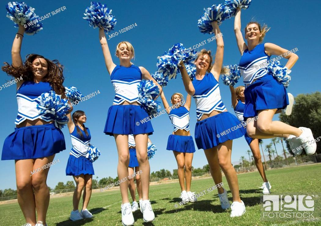 Stock Photo: Group of Cheerleaders rising pom-poms jumping on football field.