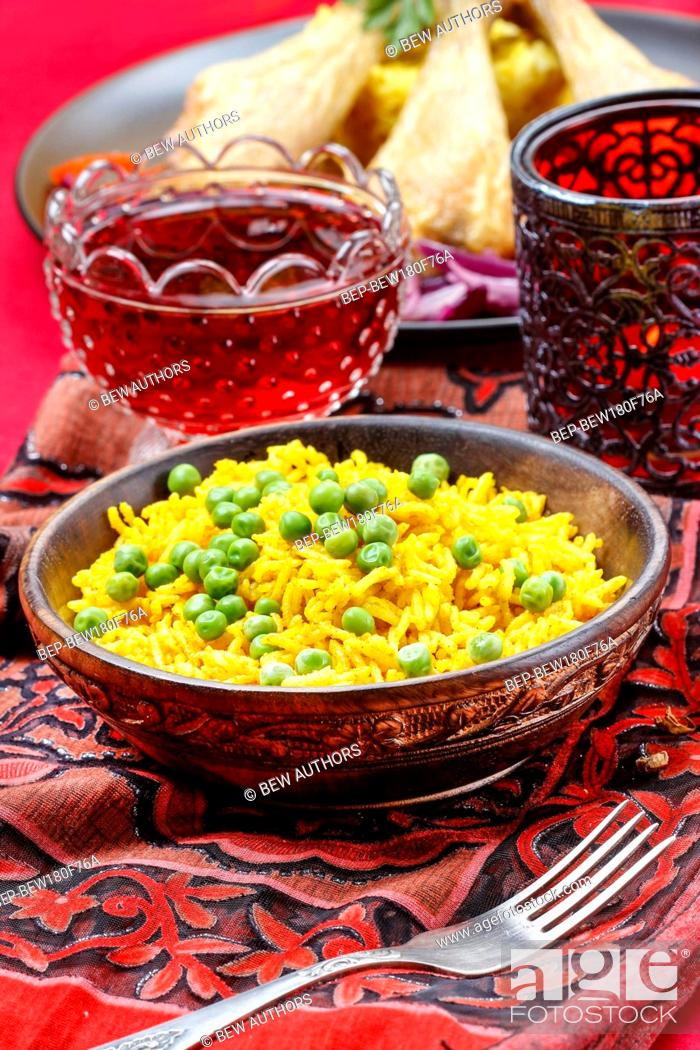 Photo de stock: Indian cuisine, bowl of yellow rice with green peas on red background.