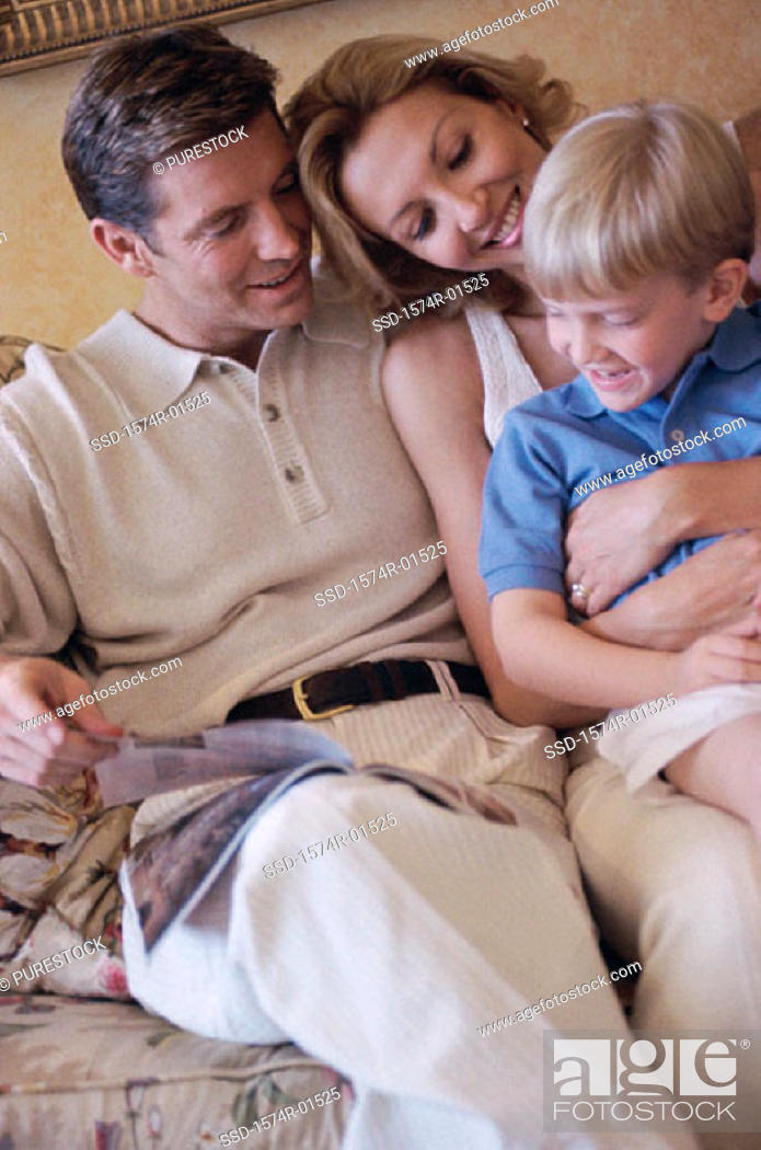 Stock Photo: Parents and their son sitting together in bed.