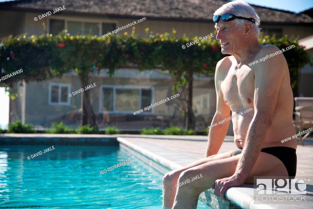 Stock Photo: Senior man sitting on edge of outdoor swimming pool.