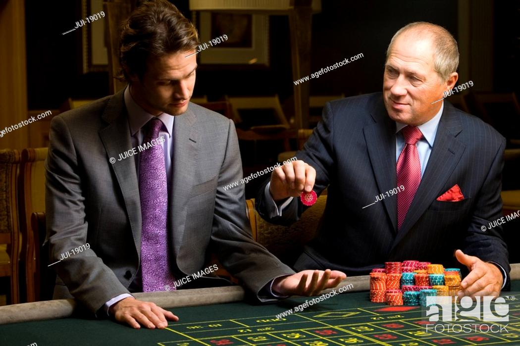 Stock Photo: Mature man with giving young man gambling chip at roulette table.
