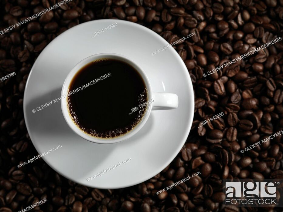 Stock Photo: Cup of coffee standing on coffee beans.