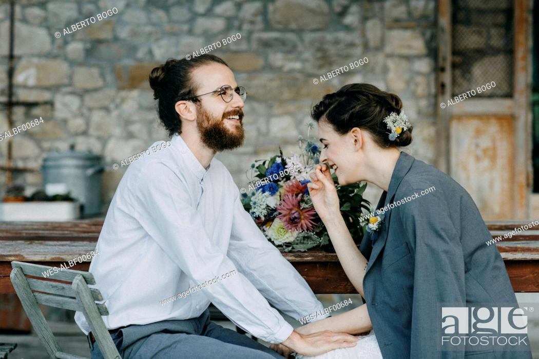 Stock Photo: Happy bride and groom sitting at table.
