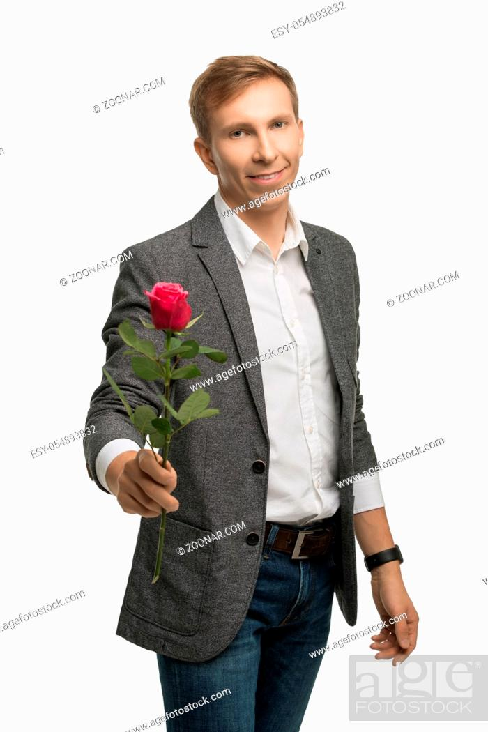 Stock Photo: Young fair handsome man wearing white shirt, jacket and jeans giving a red rose with a gentle smile cropped isolated shot.