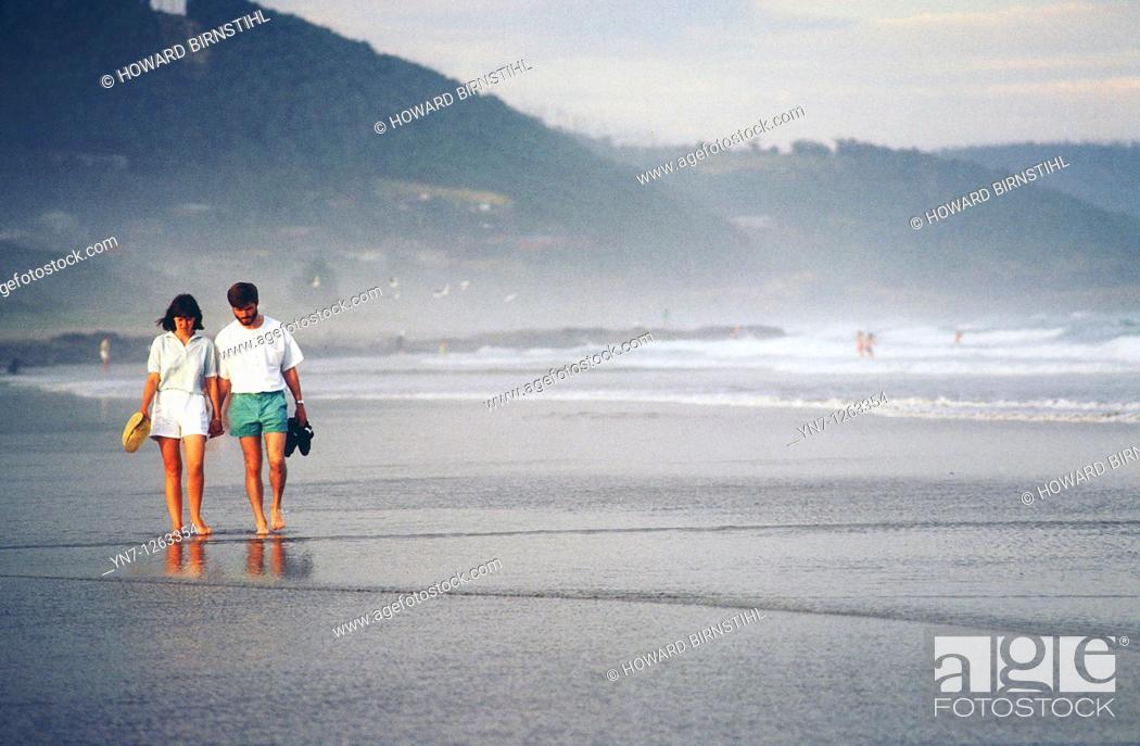 Stock Photo: Couple wandering along misty beach.